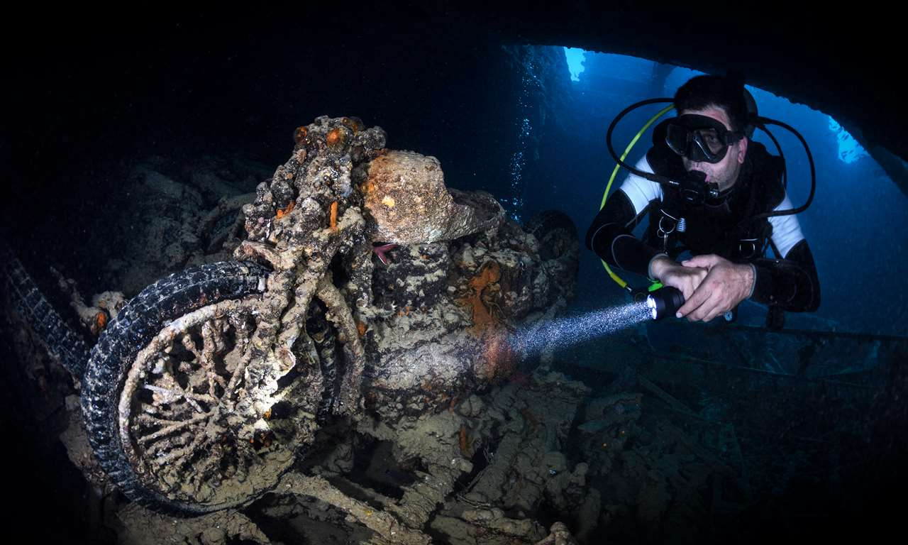 A motorcycle overgrown with corals being explored by a scuba diver with a flashlight deep inside a ship hull under the sea.